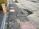 Trip hazard caused by loose paving slab and hole